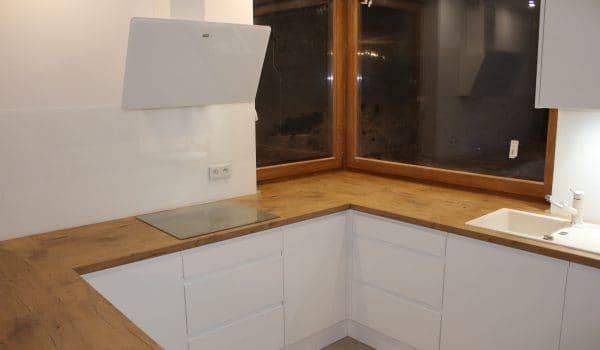 Kuchnia biała matowa z blatami wpuszczonymi pod okno.